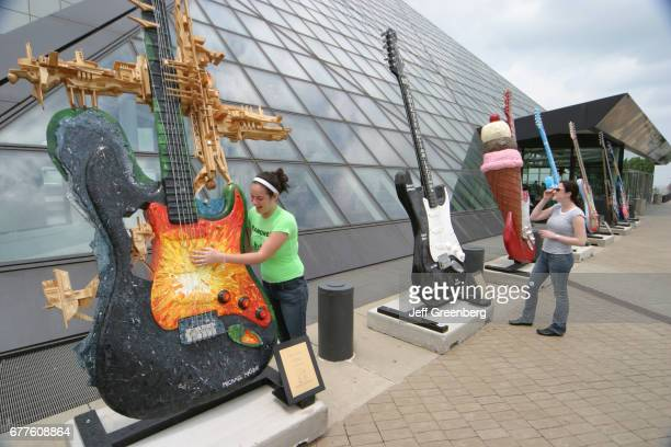 Two teen girls looking at Guitarmania statues outside the Rock and Roll Hall of Fame
