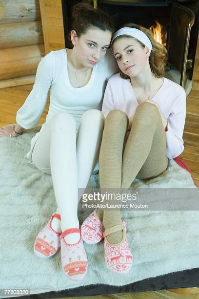 two teen girls sitting by fireplace, wearing tights and slippers, looking at camera, full length - little girls in tights stock photos and pictures