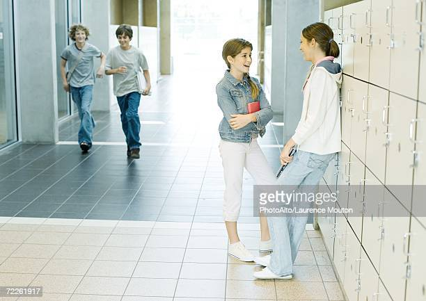 Two teen girls talking by lockers while boys run through hallway