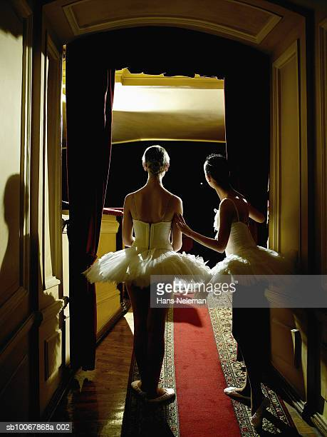 two teenage ballet dancers (14-15) waiting in wings, rear view - 舞台裏 ストックフォトと画像