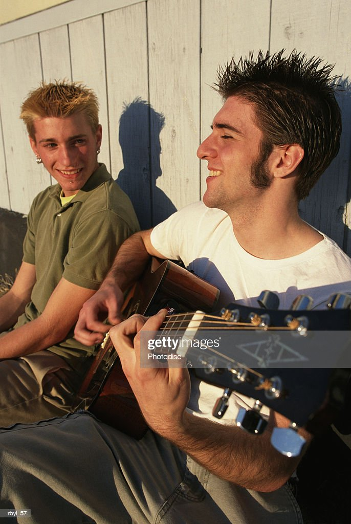 two teenage boys are sitting on a city sidewalk playing the guitar and talking to eachother : Foto de stock