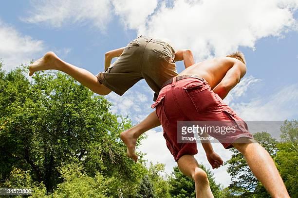 two teenage boys bouncing high in the air - endast tonårspojkar bildbanksfoton och bilder