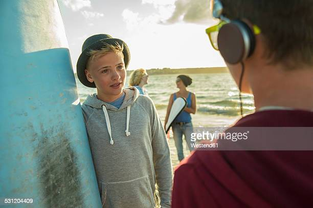Two teenage boys communicationg on the beach