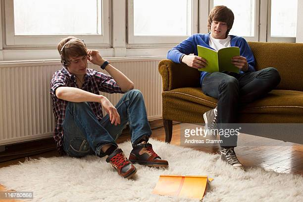 two teenage boys hanging out in a living room - 18 19 years stock pictures, royalty-free photos & images