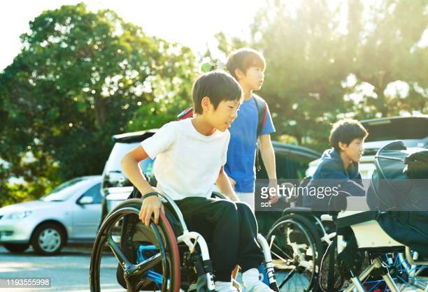 two teenage boys in a wheelchair pushing their tennis wheelchairs to play tennis - persons with disabilities ストックフォトと画像