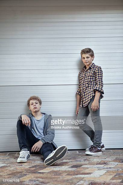 Two teenage boys leaning against a wall