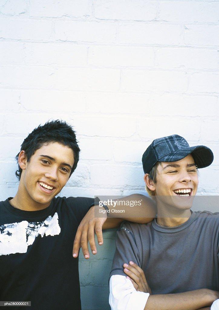 Two teenage boys leaning against brick wall, portrait : Stockfoto