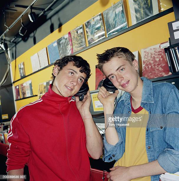 Two teenage boys (15-18) listening to headphones in record shop