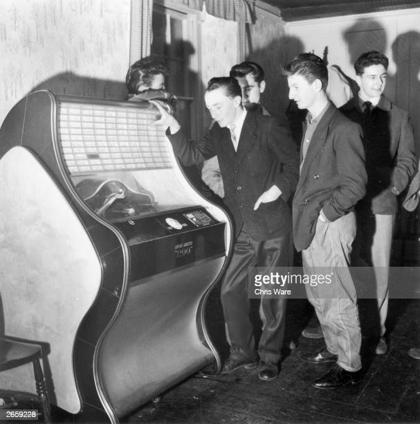 Two teenage boys listening to the latest hits on a pub jukebox.