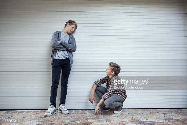 Two teenage boys looking at each other and discussing