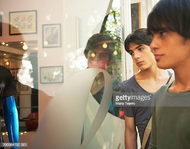 Two teenage boys (14-17) looking into shop window