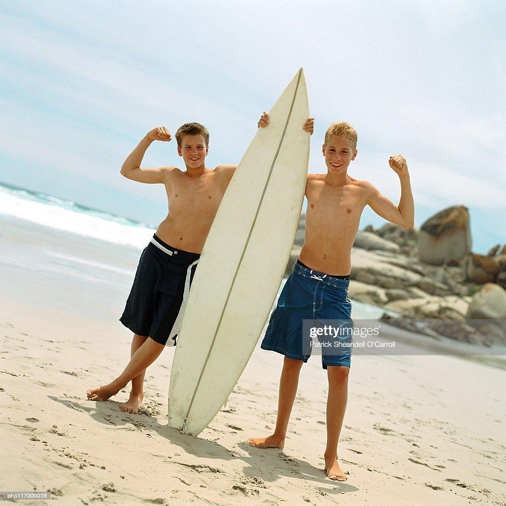 Two teenage boys on beach holding surfboard : Stockfoto