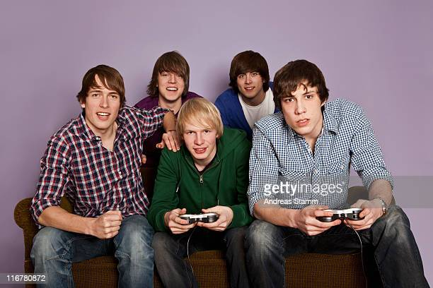 Two teenage boys playing a video game while their friends cheer them on
