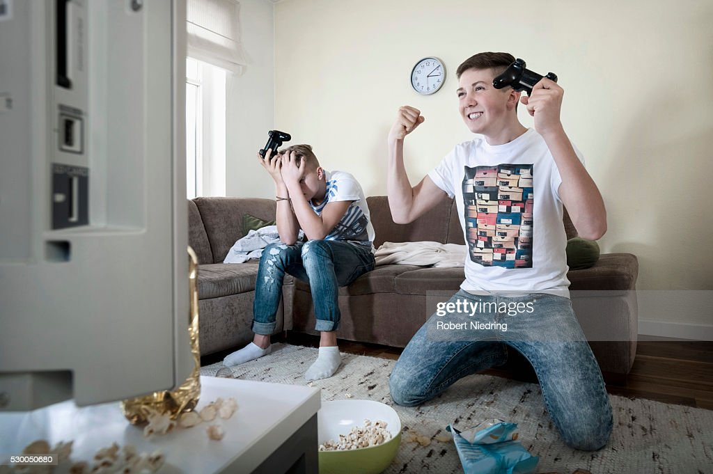 Two teenage boys playing video game : Stock Photo