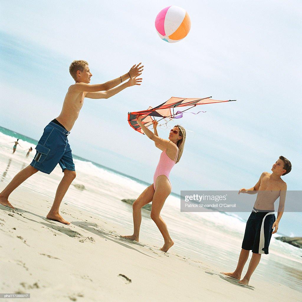 Two teenage boys playing with beach ball, girl holding kite : Stockfoto