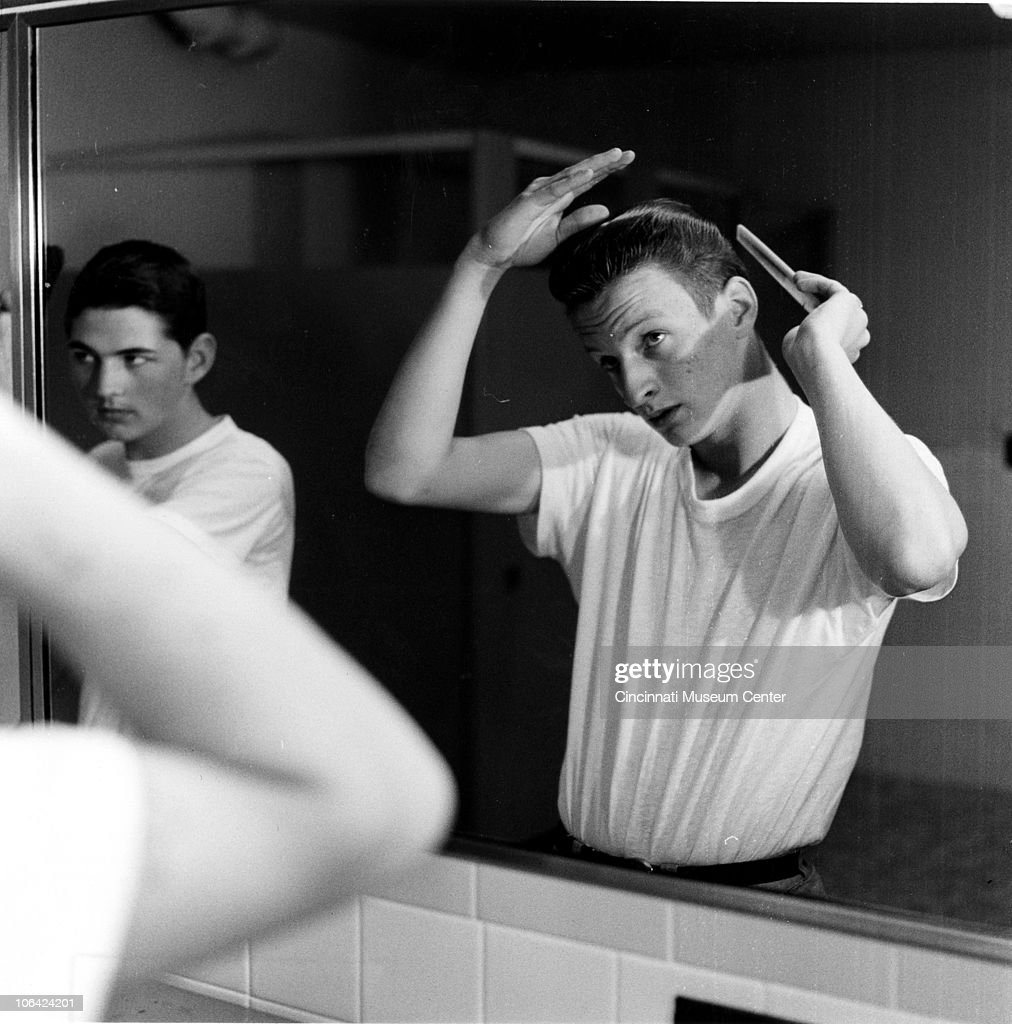 Two teenage boys primp and comb their hair in front of the bathroom mirror at the Children's Home, Cincinnati, OH, mid to late twentieth century.