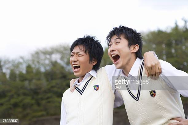 Two teenage boys putting arms around each other and yelling, front view, Japan