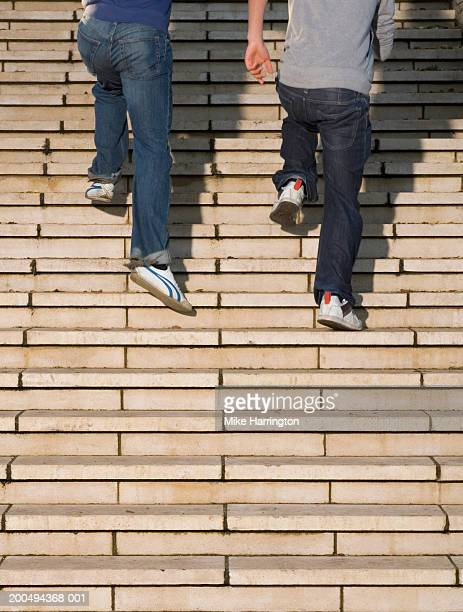 Two teenage boys (14-16) running up steps, low section
