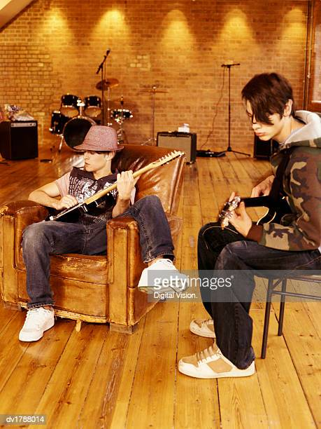 Two Teenage Boys Sit in a Studio on a Stool and Leather Armchair Composing Music on Electric Guitars
