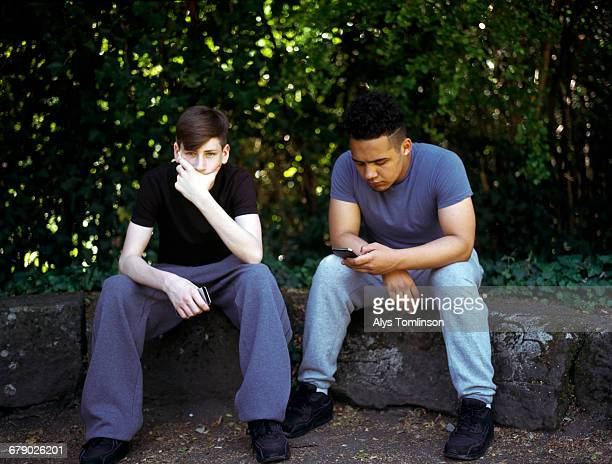 Two teenage boys sitting in a park
