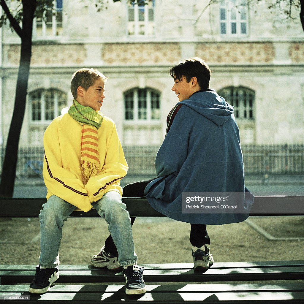 Two teenage boys sitting on bench, smiling, building in background : Stockfoto