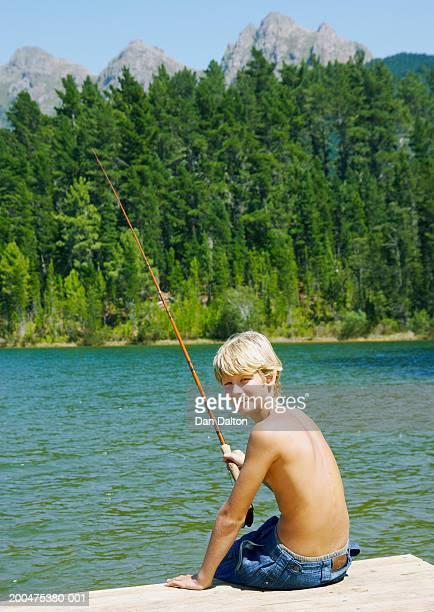 Two teenage boys (12-14) sitting on jetty, fishing, smiling, portrait