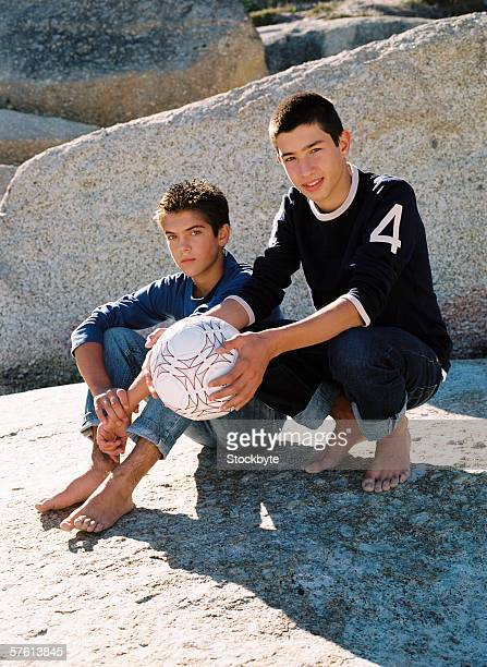 Two teenage boys (14-16) sitting on the rocks holding a football