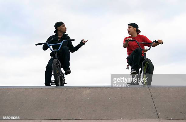 Two Teenage Boys talking on their BMX Bikes