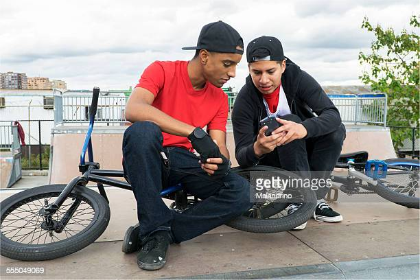 Two teenage boys texting on a mobile