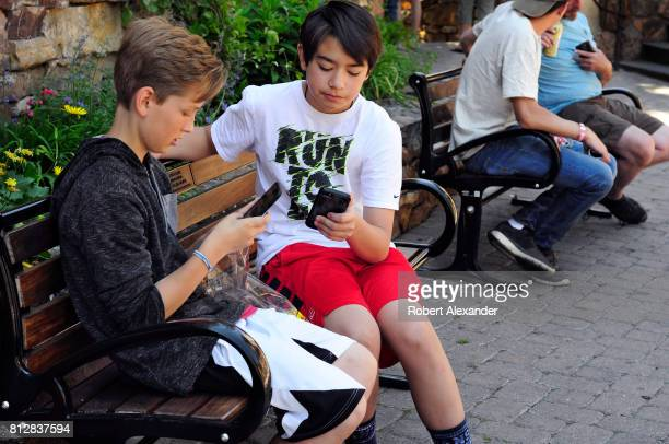 Two teenage boys use their smartphones as they sit on a bench in Vail Colorado