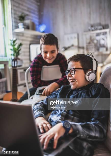 dos adolescentes con aparatos en el sofá en casa - preadolescente fotografías e imágenes de stock
