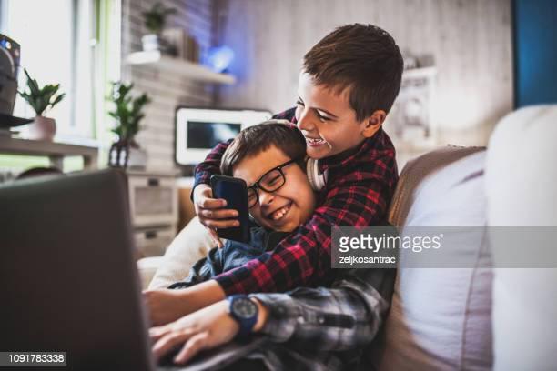 dos adolescentes con aparatos en el sofá en casa - hermanos fotografías e imágenes de stock