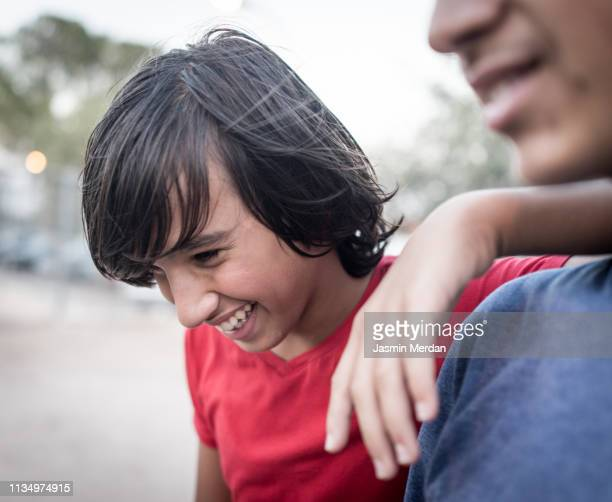 Two teenage candid boys laughing outdoors