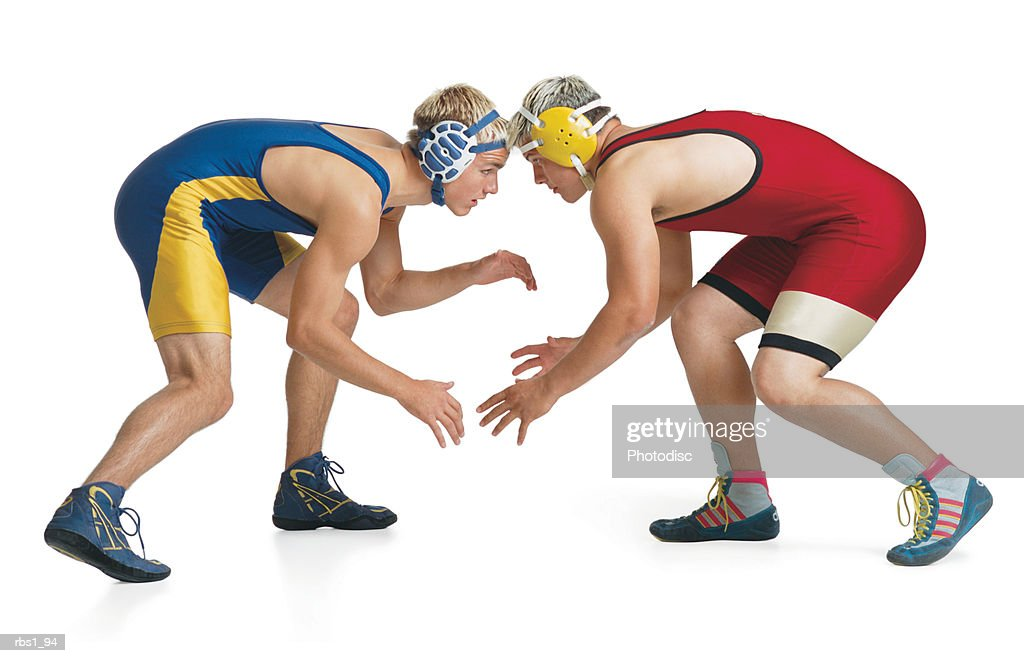 two teenage caucasian male wrestlers from opposing teams face off at the beginning of a match : Foto de stock