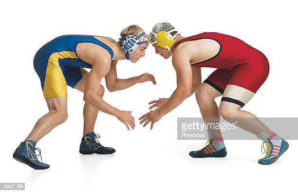 two teenage caucasian male wrestlers from opposing teams face off at the beginning of a match - wrestling stock pictures, royalty-free photos & images