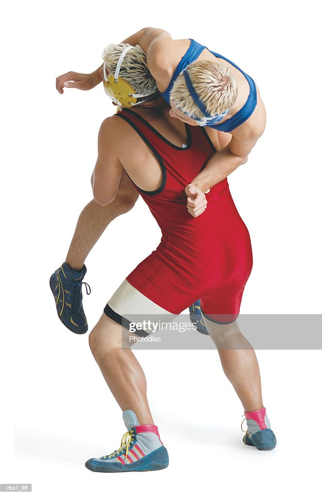 two teenage caucasian male wrestlers from opposing teams fight as the one in red lifts up the one in blue : Foto de stock