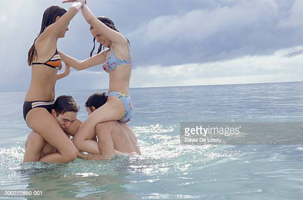 Two teenage couples (16-17) engaged in chicken fight at the seashore, side view