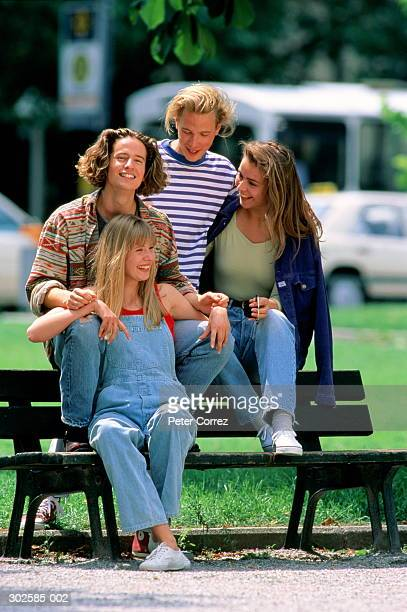 Two teenage couples sitting on park bench