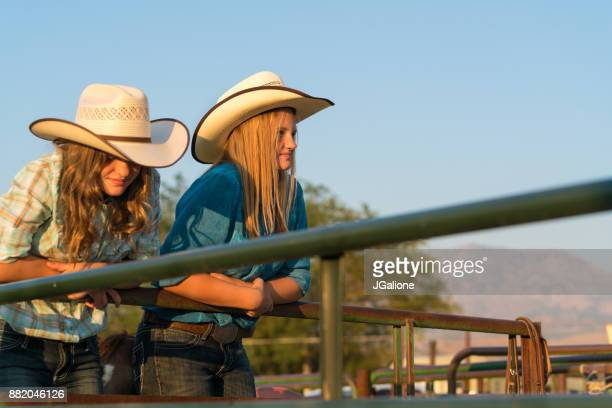 Two teenage cowgirls leaning on a metal fence