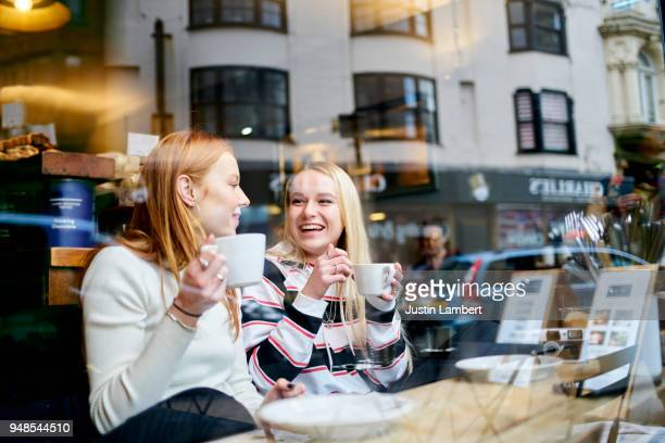 two teenage female friends enjoying a coffee and a moment together sitting in a cafe window - coffee shop stock photos and pictures