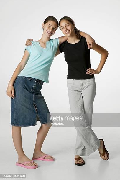 two teenage friends (14-15) side by side, posing in studio, portrait - alleen tienermeisjes stockfoto's en -beelden