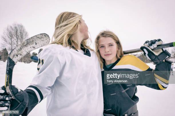 Two teenage girl ice hockey players standing on rink outdoors in winter
