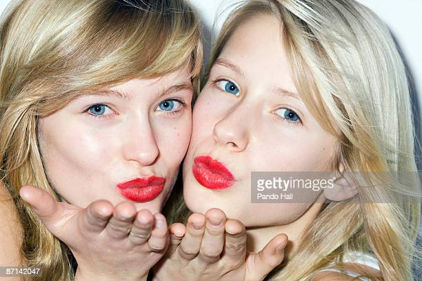 Two Teenage Girl with red lips blowing kiss