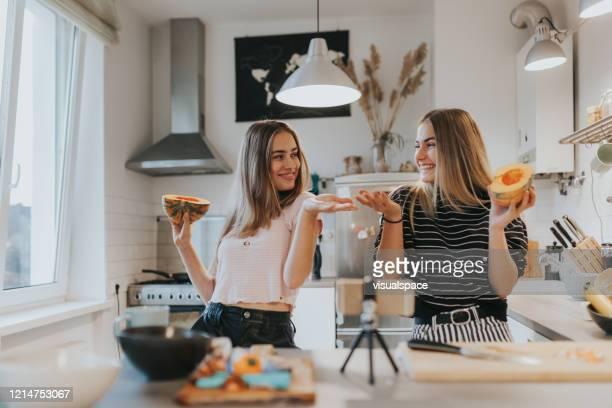 dos novias adolescentes filmando un video musical en la cocina con teléfono inteligente - influencer fotografías e imágenes de stock