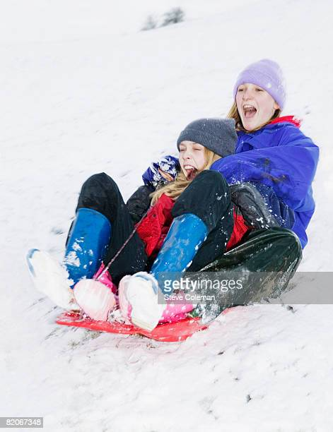 Two teenage girls, 13 years and 14 years old, sliding down hill on sledge