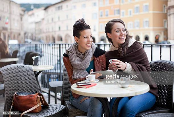 two teenage girls at a café, using digital tablet