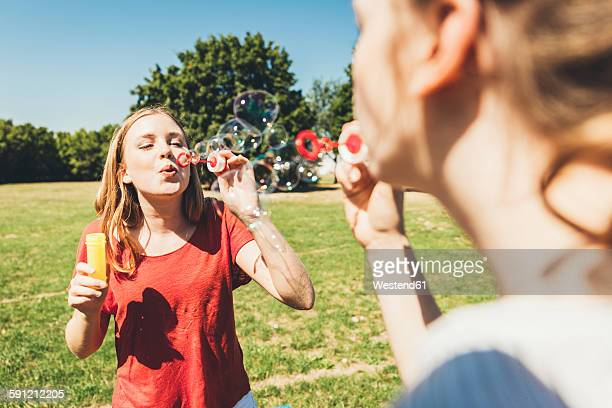 Two teenage girls blowing soap bubbbles in park