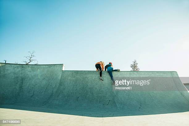 two teenage girls climbing in skatepark - ハーフパイプ ストックフォトと画像