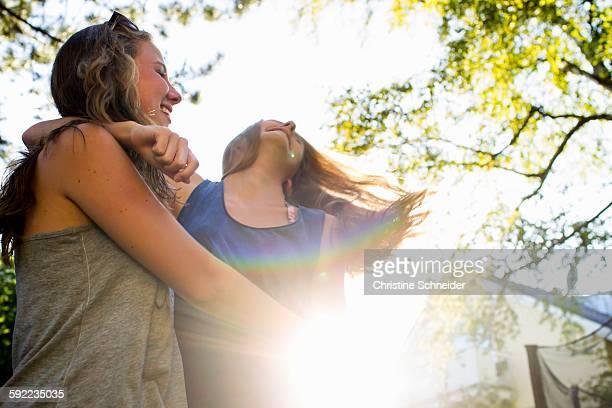 Two teenage girls dancing in sunlit park