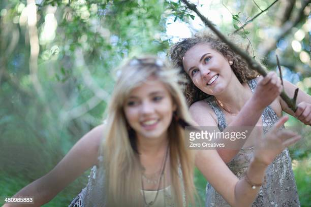 Two teenage girls discovering woodland